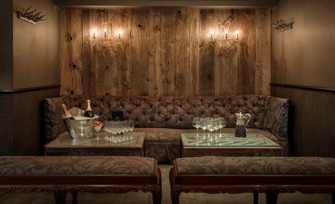 a alcove area in a restaurant with a wooden back wall. There is a large sofa in the corner with a paisley print and two matching benches opposite. In-between this furniture are two small glass coffee tables with a ice bucket, bottle of prosecco and glasses on it.
