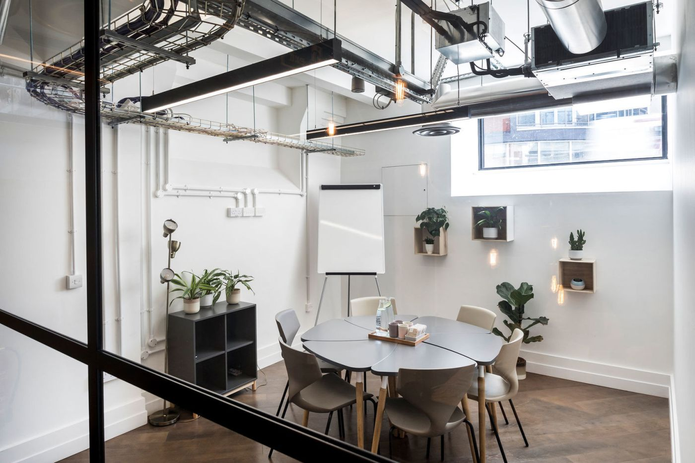 A white meeting room in London with a grey table and chairs and green plants
