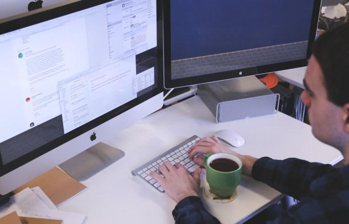 man staring at two computer screens
