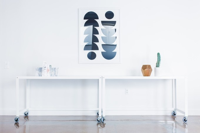 white room with two desks underneath mounted art
