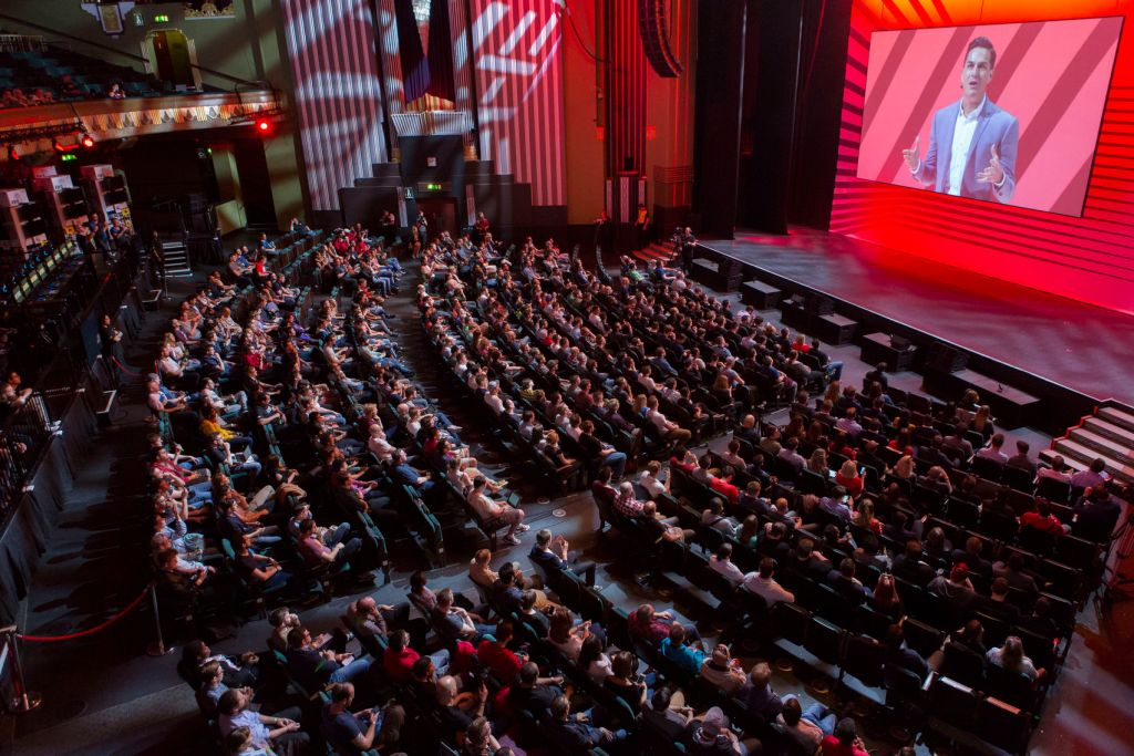 A large event space with theatre style seating full of people and facing a stage and big screen on the back wall