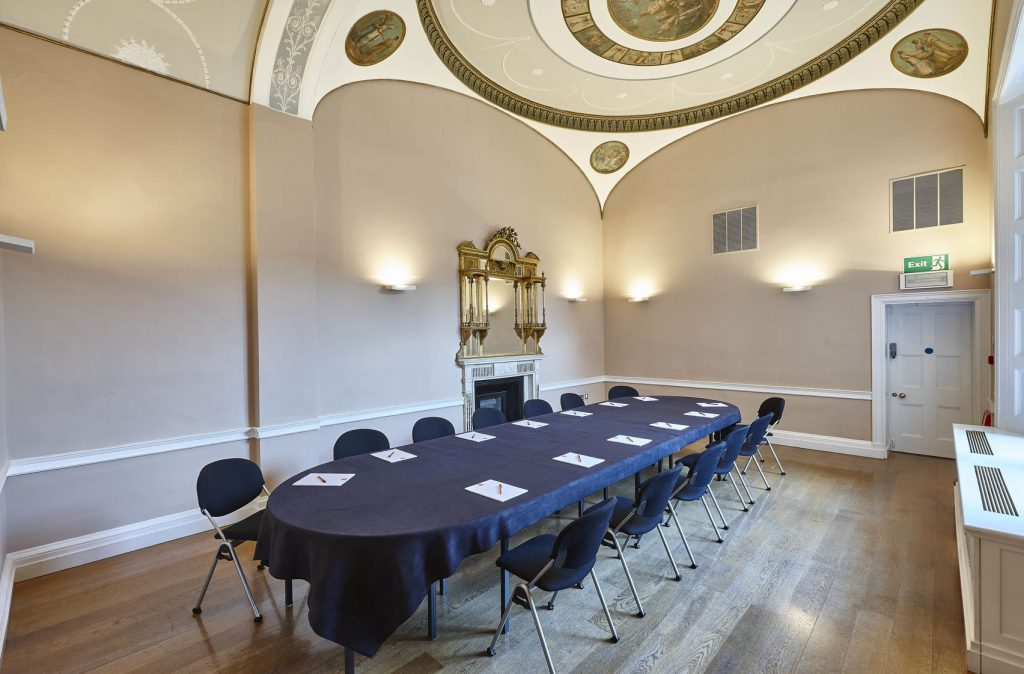 A large room with high ceilings. The ceiling is painted with a beautiful mural then there is an oval table in the middle of the room with chairs surrounding it.
