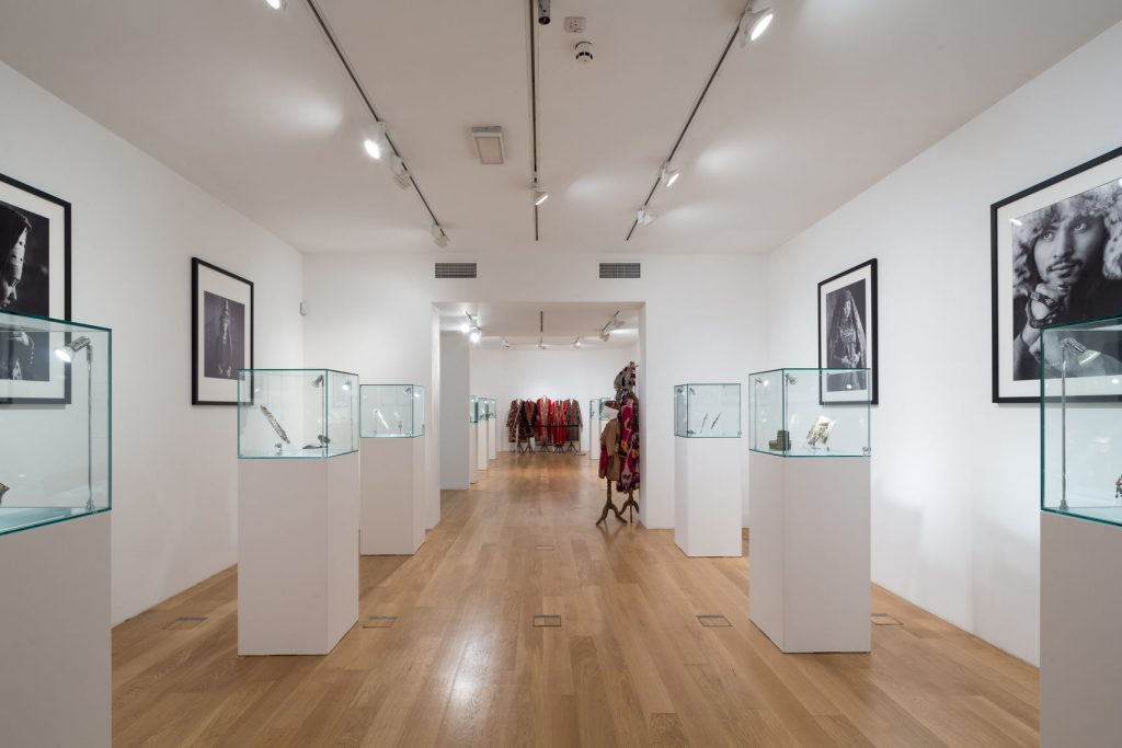 A contemporary art gallery with art on the wall and on stands in the middle of the floor