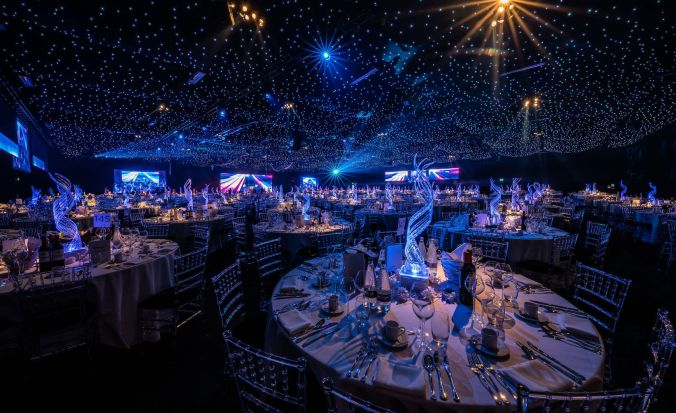 A large conference venue in London which has round tabes and blue lighting