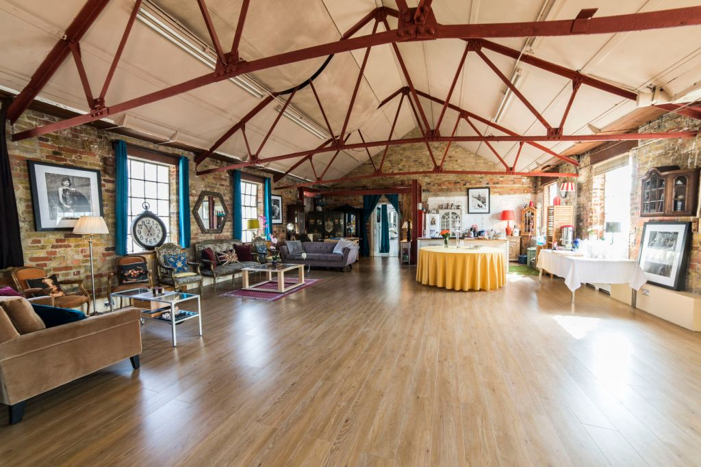 A large spacious loft with exposed metal beams and wooden floor. The loft is furnished with colouted furnishings including sofas and mirrors.