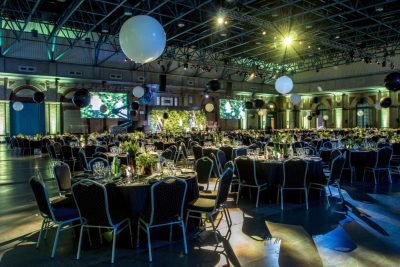 Alexandra Palace is set up in cabaret style with green and blue lighting and balloons handing from the ceilings. A beautiful Christmas party venue.