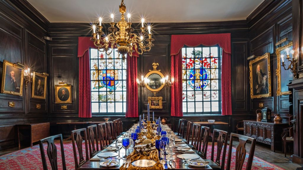 A historic hall in London. The Space has dark wood panelling on the walls with oil paintings hanging from the walls. There are two large stained windows at the rear of the space which are draped in red velvet curtains.