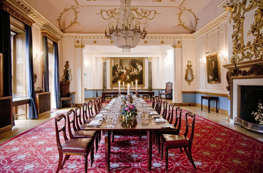 The Court Room at Stationer's Hall is a boardroom which has a dark wooden table in the middle and ornate detail on the ceiling and walls.