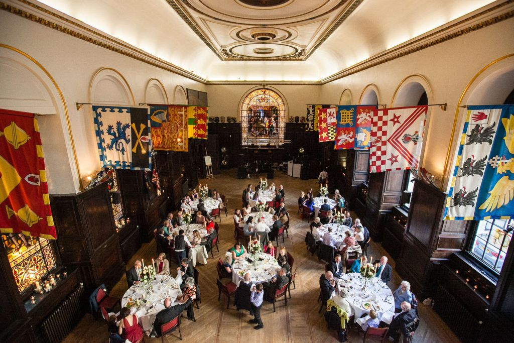 The Livery Hall at Stationer's Hall is a large livery hall with stained glass windows, flags hanging from the walls and 9 cabaret tables with people sat around them.