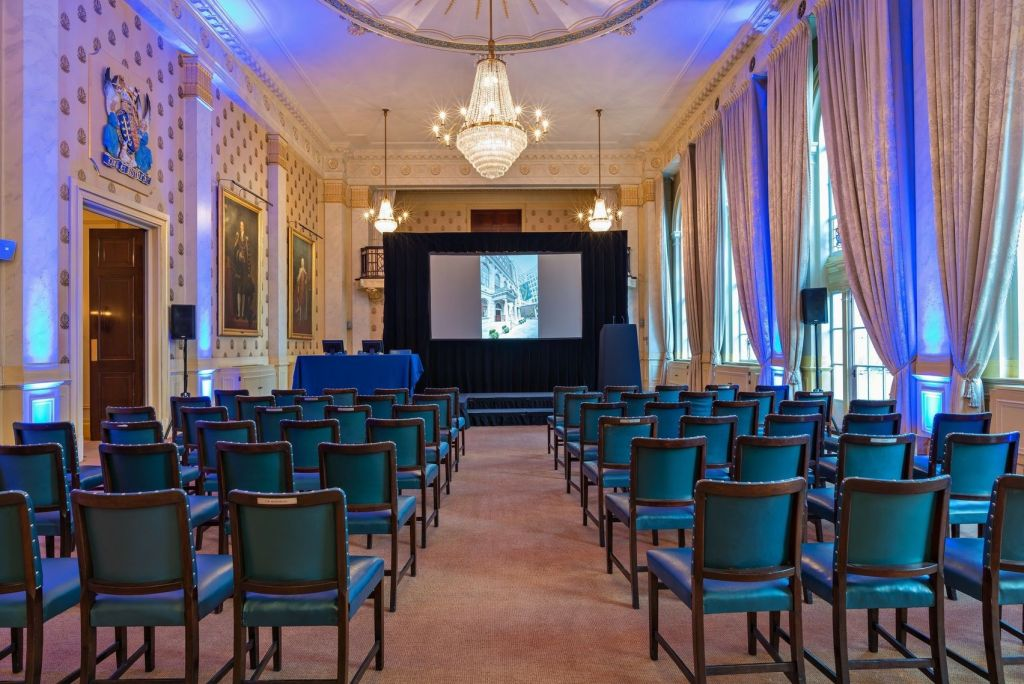 A large hall hire in London, Saddlers Hall has high ceilings with dramatic curtains draped over the windows. The room is set out in conference room style with chairs facing a screen.