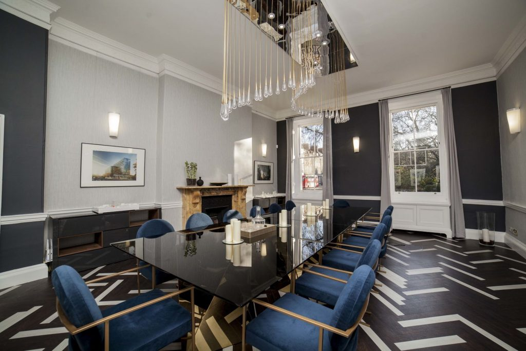 A stylish boardroom with a large glass table in the centre which is surrounded by blue velvet chairs and has a large light suspended above it.