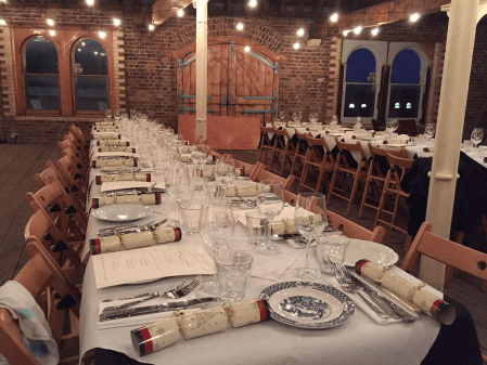 an attic style event Space with exposed brick walls and arched windows has a large table set up in the centre of the room. The table has been set up for christmas with crackers and wine glasses on it at Menier Spaces