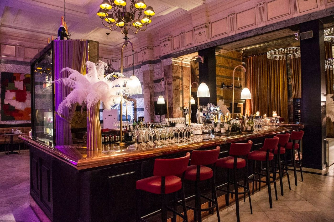 A grand venue which has high ceilings and marble pillars. The image has the focus on the island bar in the middle of the room which is surrounded by red leather bar stools and has a range of glasses on the bar and feathers decorating the corner. A truly extravagant Christmas party venue in London