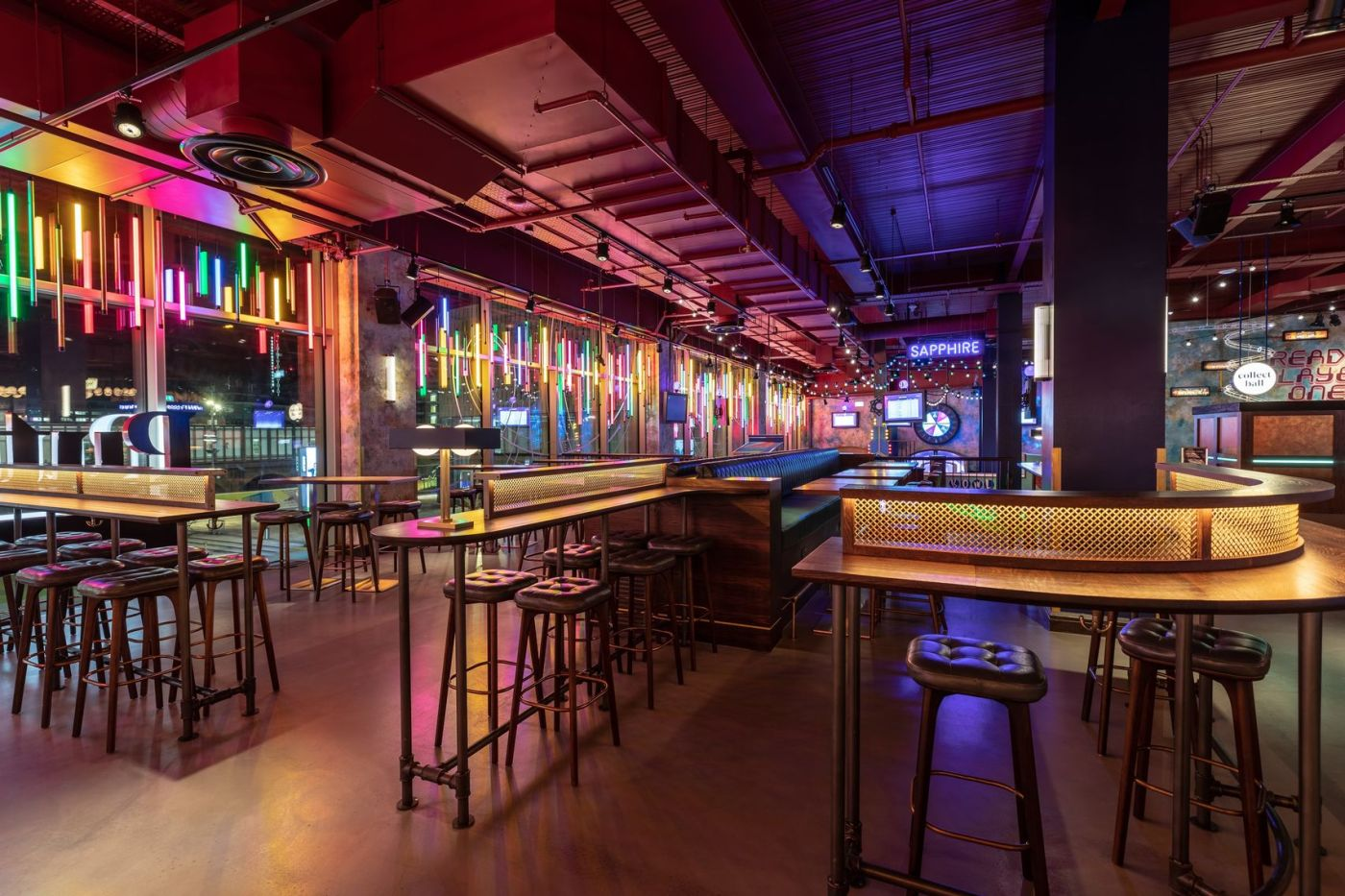 A modern, contemporary bar puttshack is also a mini golf course. You can see bar stools and tables and the glass wall on the left hand side is lit up with multi-coloured hanging lights.