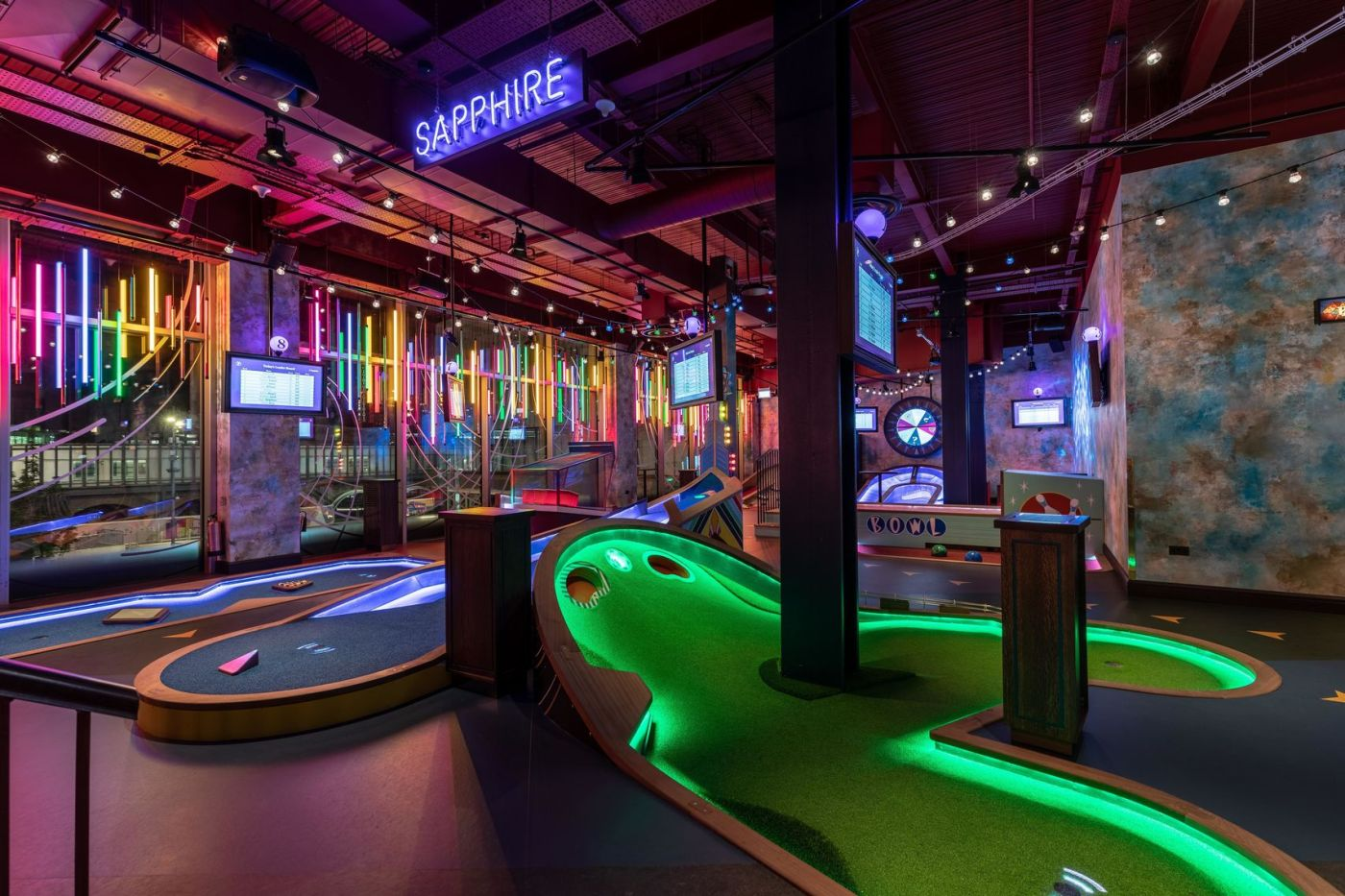 An interactive mini golf course in the city called Puttshack. You can see the different mini golf activities on the floor then the venue is decorated with bright lights.