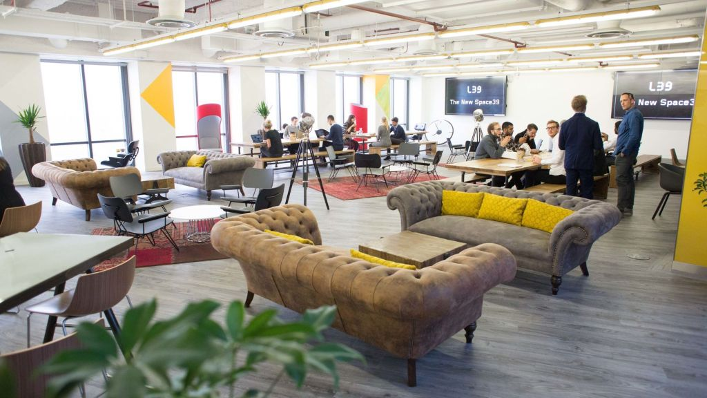 A large networking area with different coloured sofas