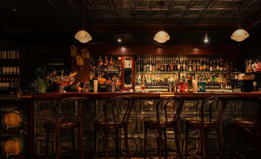 Nightjar is the ultimate christmas party venue in London. A late night speakeasy you can see the bar in the background with 5 bar stools. The decor of Nightjar is dark greens and browns.