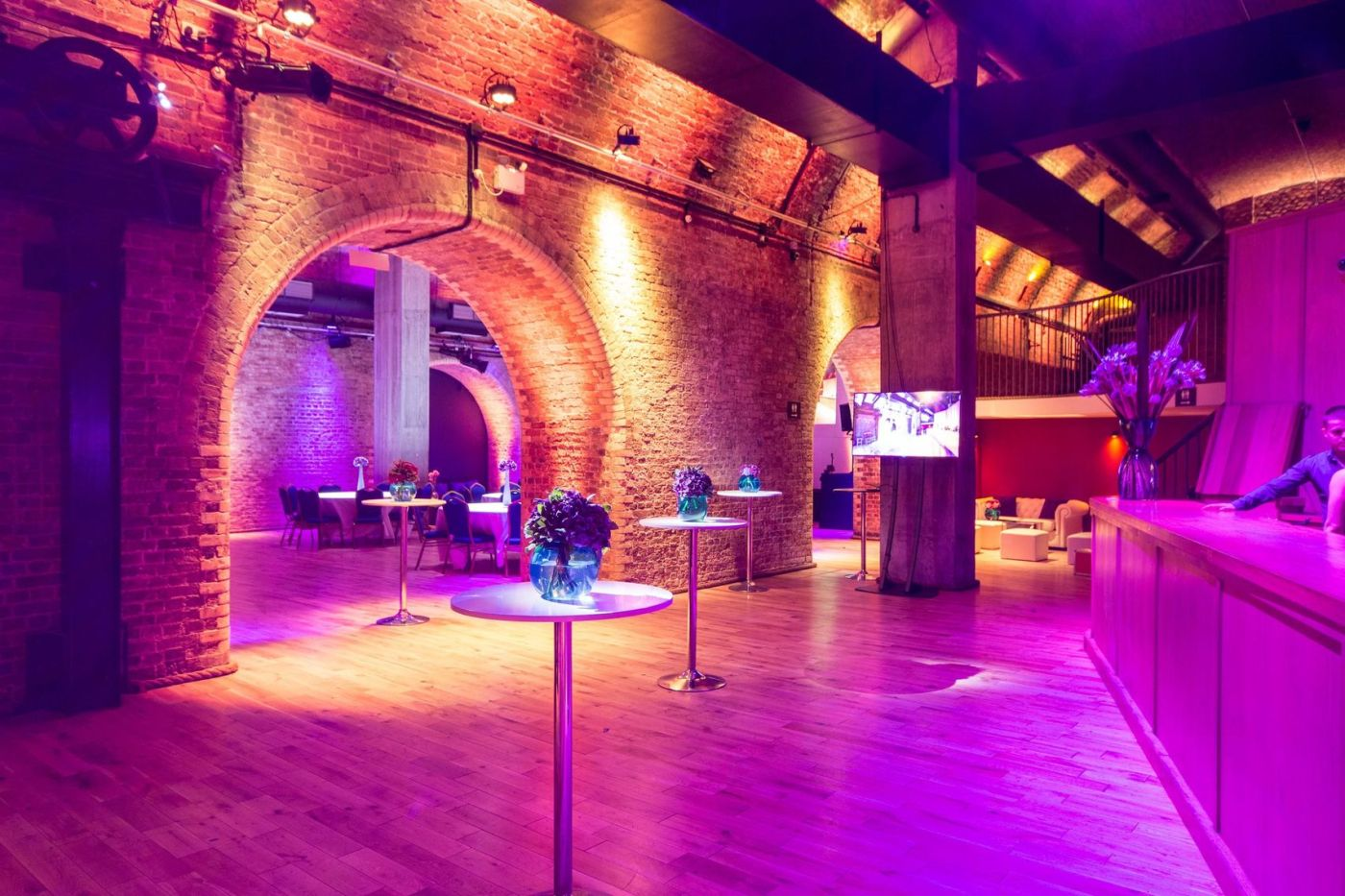A large event space with exposed bricks and arches