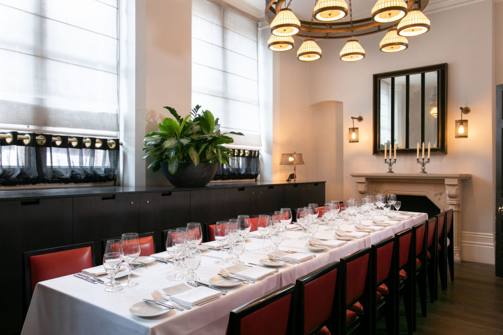 A breakfast meeting venue in London with high ceilings and a long table which is surrounded by red chairs and a circular feature light in the middle.