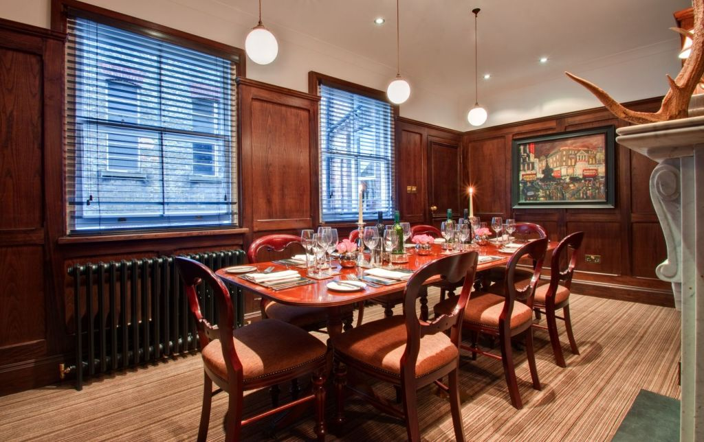 A breakfast meeting venue with two large windows and wood panelling on the walls. A wooden table is in the middle of the room and is set for dinner for 8 people.