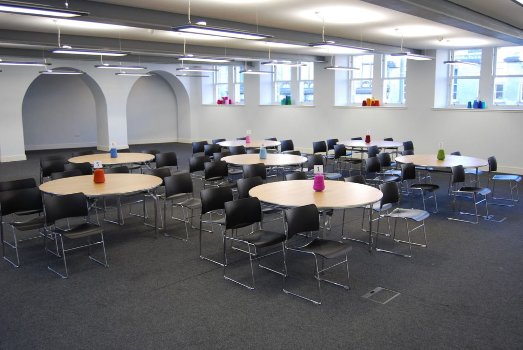 A small conference room in Edinburgh with round tables and black chairs