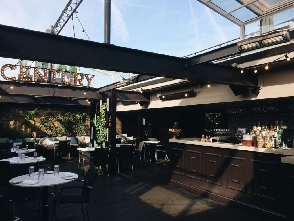 A rooftop bar which has black beams and has the word century in lights at the background