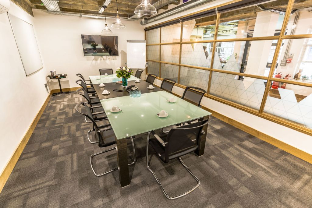 A large meeting room in London which has a tv on the back wall and a projector on the side wall.