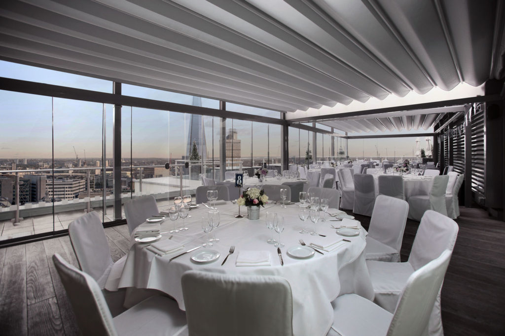 A large private dining with a view. The room has several white round tables surrounded by white chairs