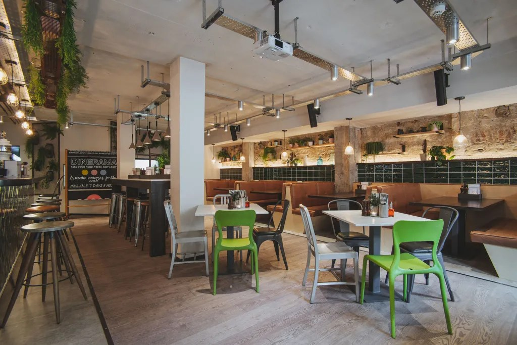 A cosy restaurant in Edinburgh with exposed walls and tiles and different coloured chairs.