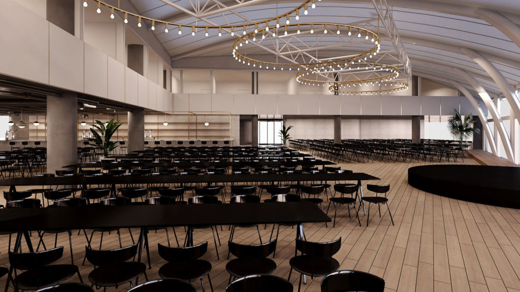 large conference venue with long black table and chairs set out