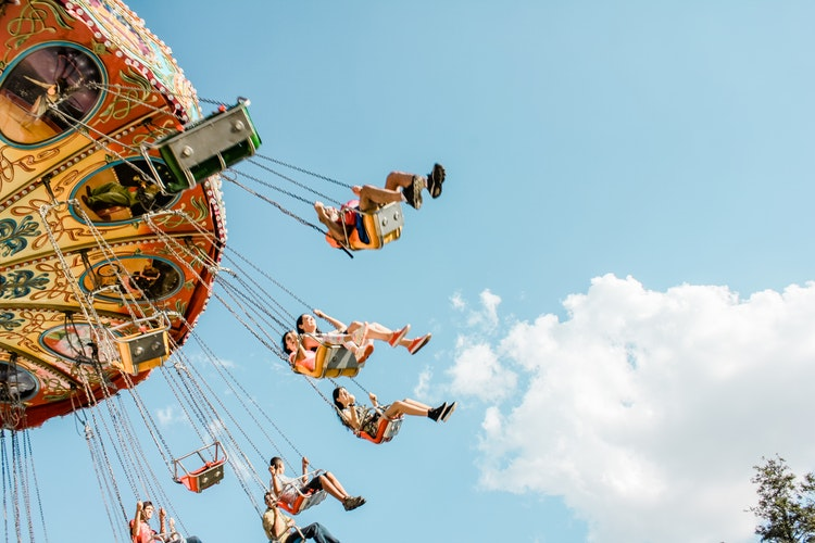 People swinging on chairs on a fairground ride..