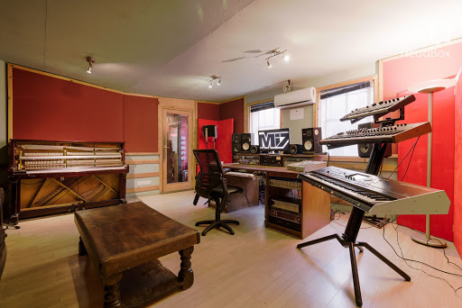 A recording studio in London with red walls and multiple keyboards. The perfect recording studio hire London.