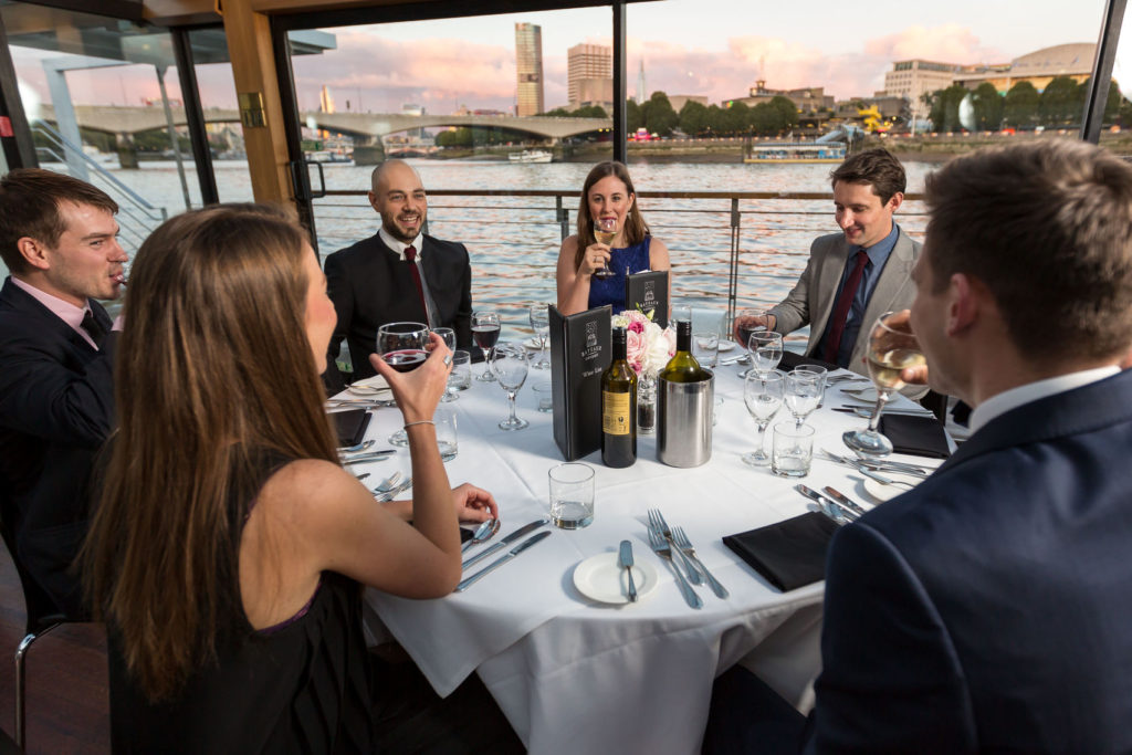 A party of guests enjoy wine at a round table on a boat on the River Thames