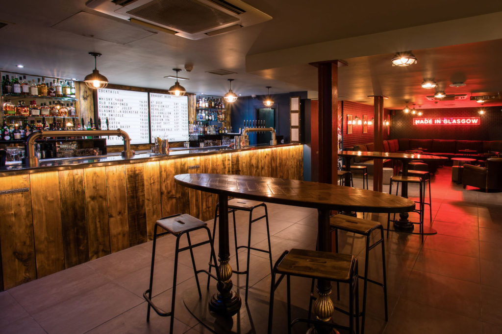 A bar area with subtle lighting and wooden chairs at wooden tables with a cushioned seating area at the back of the venue