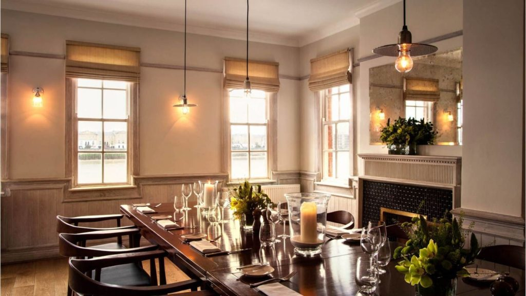A long, private dining table at The Narrow with candles, wine glasses and table decorations
