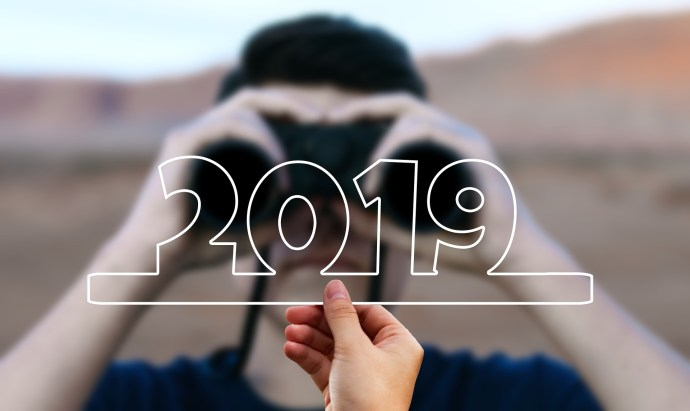 A man holding binoculars with the outline of 2019 in front of them.