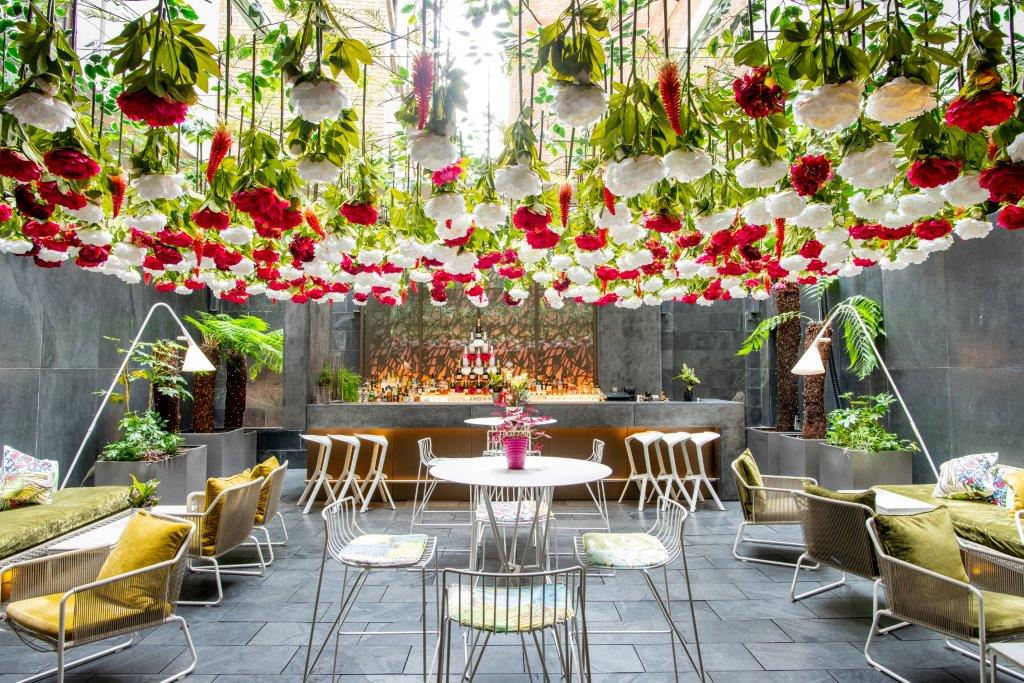 An outdoor garden with yellow and gold chairs and roses hanging from the ceiling