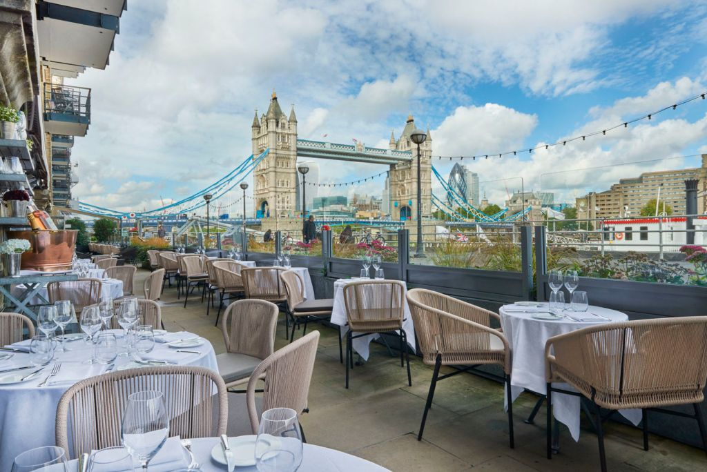 An outdoor restaurant terrace with a view of Tower Bridge.