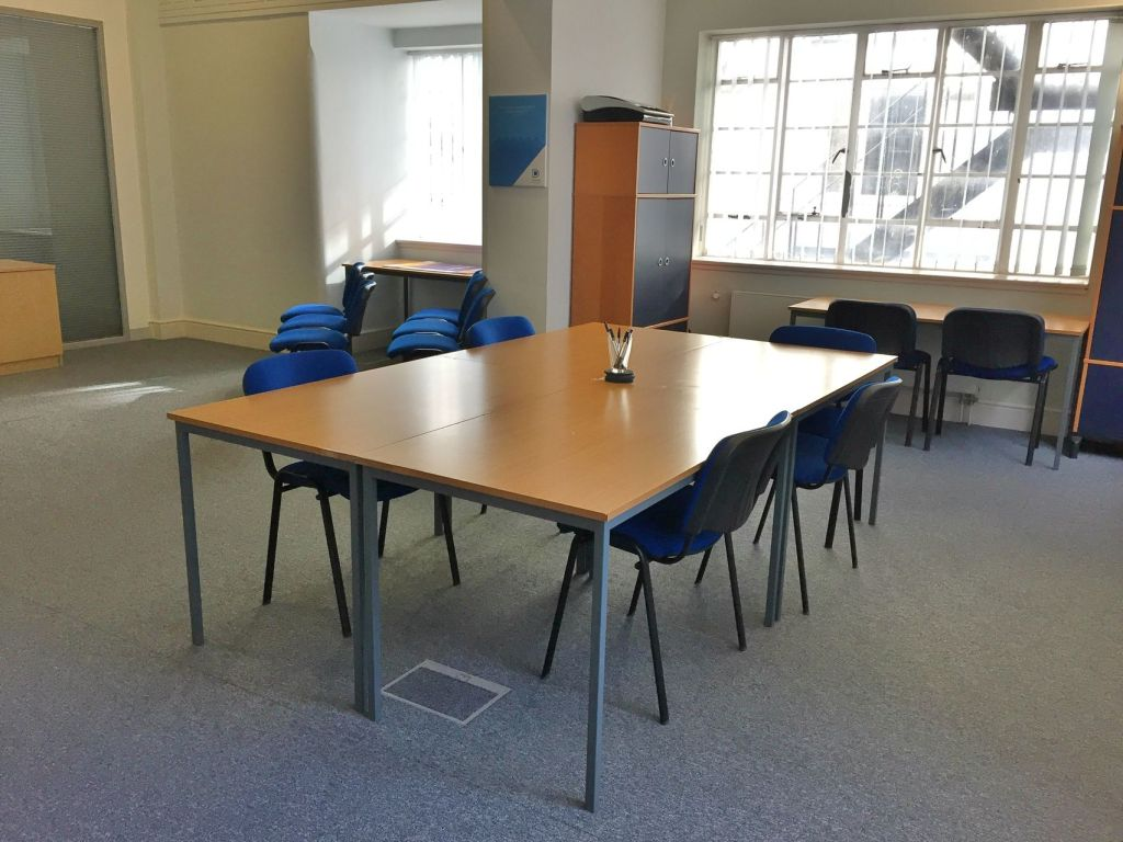 Large open room with wooden table with four blue chairs and large windows with cupboards