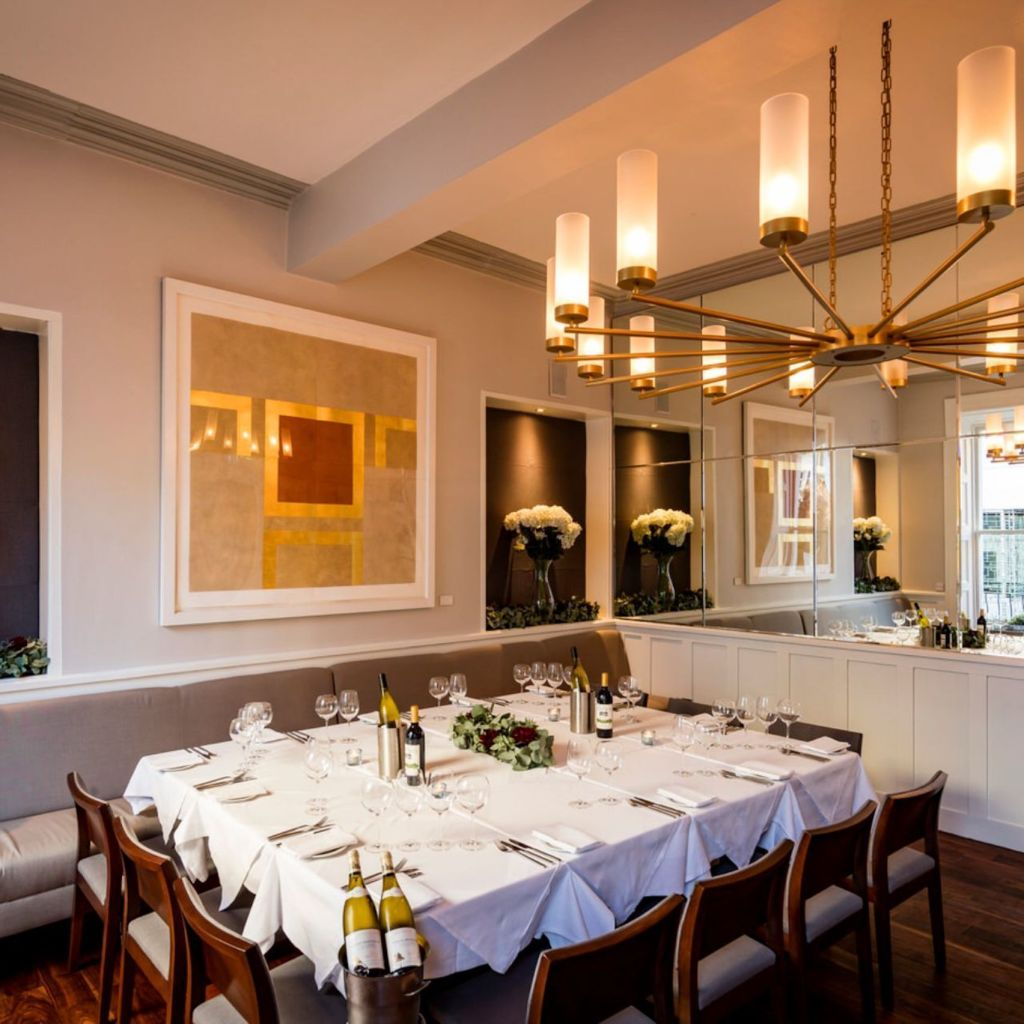 private dining room with table with white tablecloth and white lighting with pictures on the wall