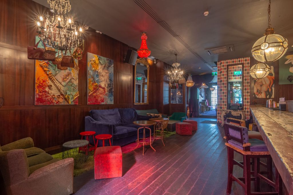 Private bar area with sofas and stools with hanging lights and wooden panelled walls