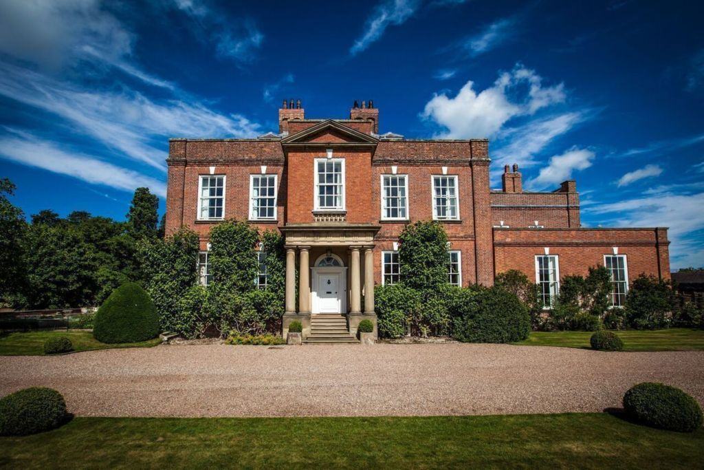 A large red brick country manor which is surrounded by plenty of land with lots of greenery