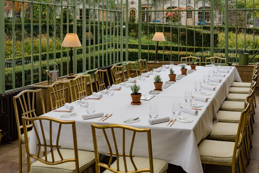 Long table with white tablecloth and wooden chairs in a conservatory space looking out onto gardens