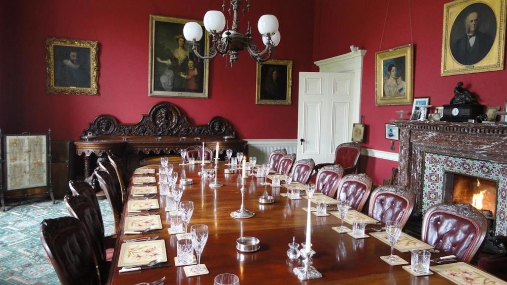 Grand dining room with wooden table with candles, fireplace, hanging lights and portraits on the wall