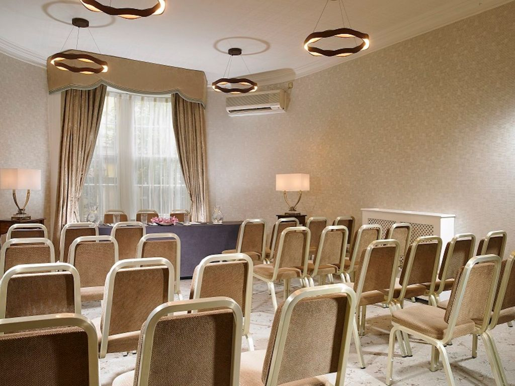 meeting room with chairs set out conference style facing a table and chairs and large window
