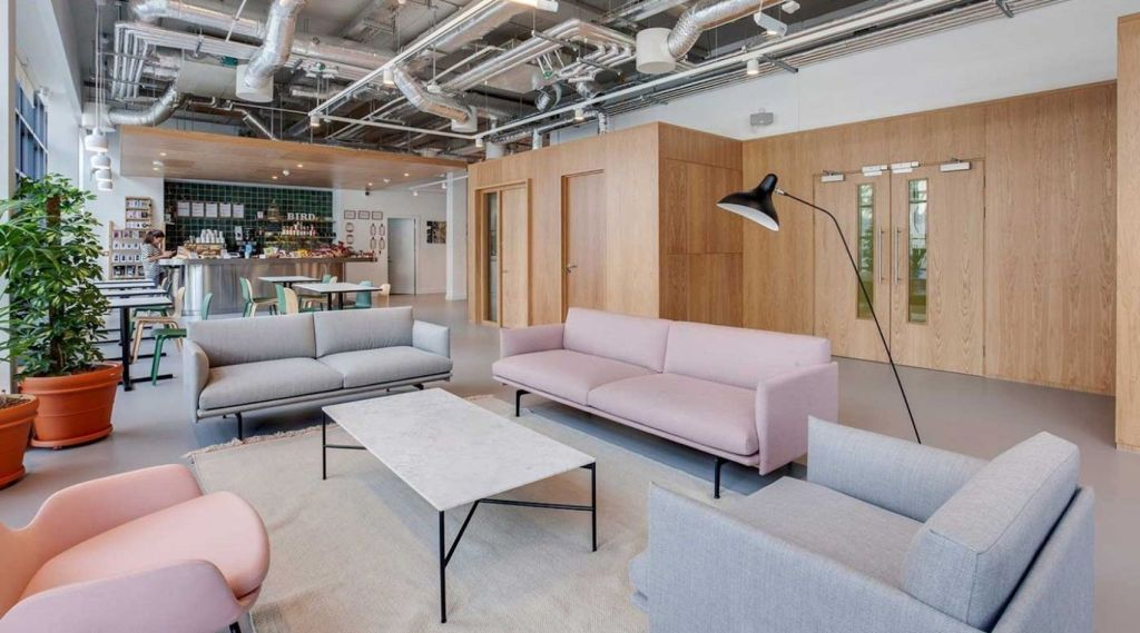 Networking area with sofas, chairs, potted plants and a refreshments area