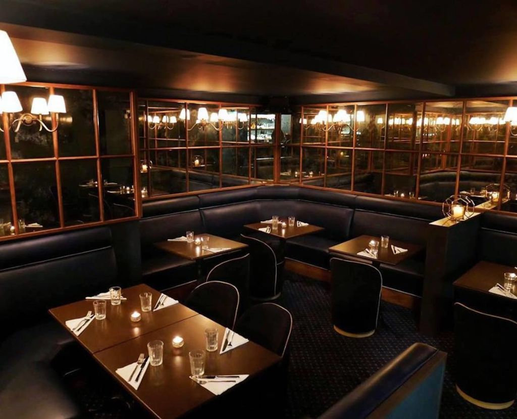 Private room with mirrored walls, wooden tables with leather chairs and tealights