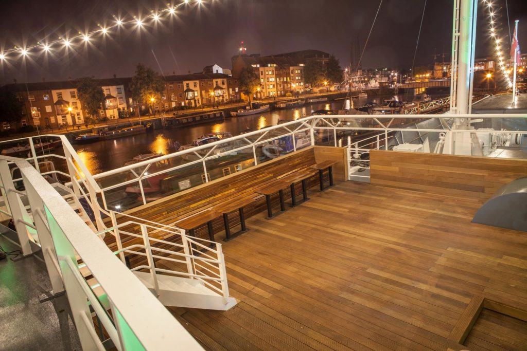 Top deck of a boat in Bristol. In the background you can see the river and the buildings lit up on the waterside
