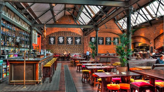 Bar area with exposed brick walls, sets of tables and chairs and stools at the bar with plants and images on the wall