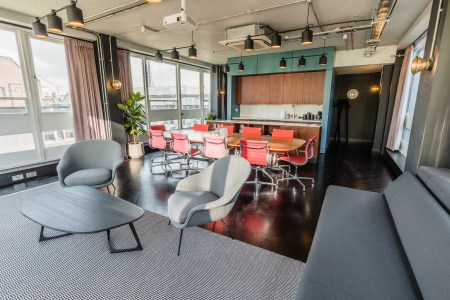 A meeting penthouse in London with grey sofas and pink chairs